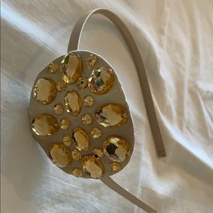 Headband. Thin gold w/ large gold emblem w/stones